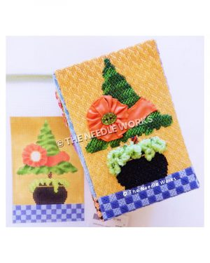 Christmas tree topiary with pink ribbon wrapped around with flower shape on orange background with blue checkered floor