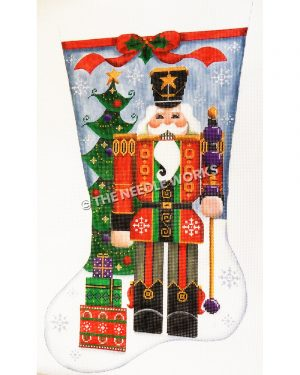 blue and white stocking with nutcracker wearing red and green suit with black and gold trim holding a gold and purple staff standing in front of a Christmas tree in the snow with gifts at the toe
