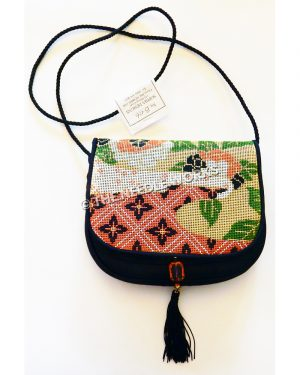 purse with red, black, gold and white pattern, green leaves, and red, white and black flowers