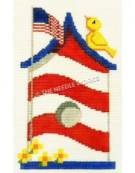 red and white striped birdhouse with blue roof and yellow bird on top of roof and American flag waving with yellow flowers at base of flag pole