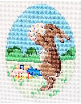 Easter egg with brown bunny holding white egg with blue dots with eggs sitting in prairie landscape with green bushes and blue sky
