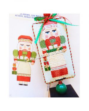 Mrs. Claus nutcracker carrying gift on tray wearing red hat and green, red and white dress