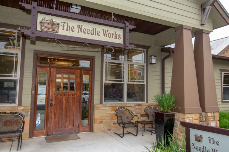 The Needle Works photograph of front entrance covered porch and sign