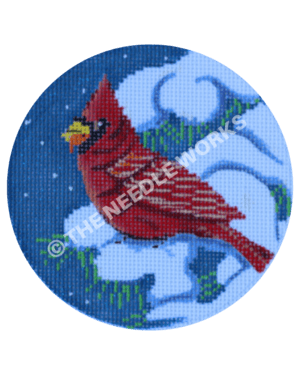 blue round ornament with cardinal on snowy tree