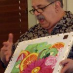 instructor Tony Minieri holding a canvas with colorful flower pattern