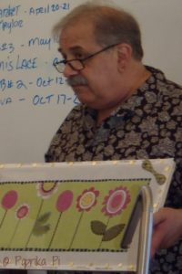 instructor Tony Minieri holding canvas with pink flowers in front of white board