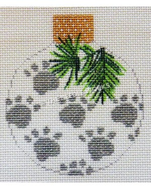 white round ornament with silver paw prints and pine needles