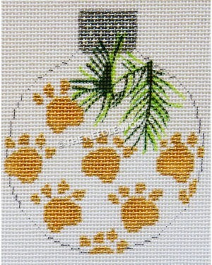 white round ornament with gold paw prints and green pine branches