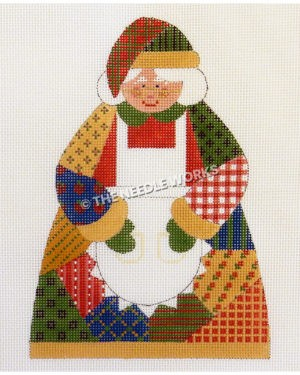 Mrs. Claus in a patchwork dress and hat in red, green, yellow, and blue wearing a white apron and holding cookies