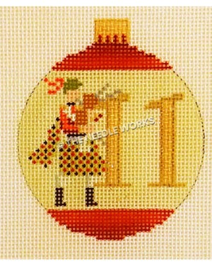 yellow and red ornament with man holding bagpipe and 11 in gold