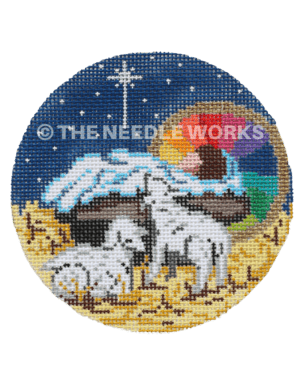 round ornament with baby Jesus in manger and two lambs next to him and starry sky background