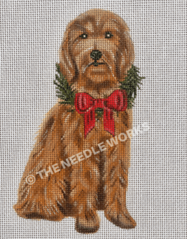 goldendoodle sitting and wearing wreath with red bow
