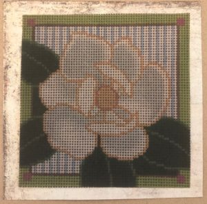 white flower in square with blue and white stripes and green border with purple squares in corner
