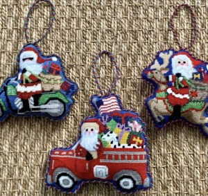 three ornaments with Santa on a motorcycle, fire truck, and reindeer with bags full of gifts