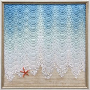 gold framed square with ocean water touching sand with orange starfish accent